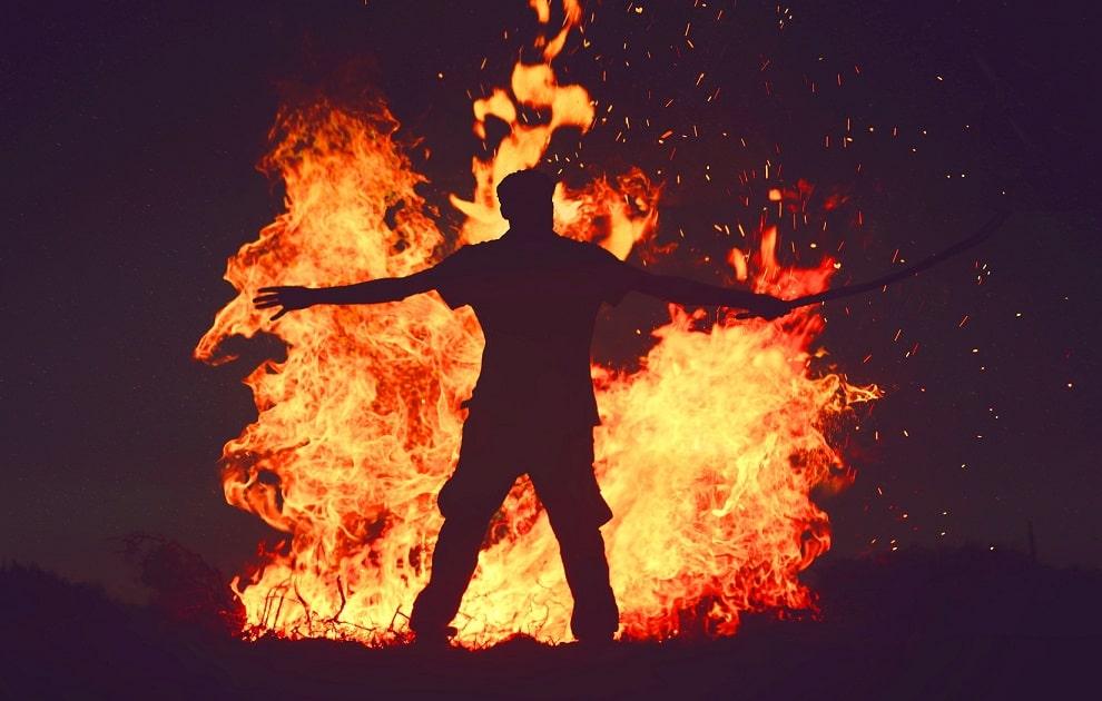 barbat in fata unui foc de tabara
