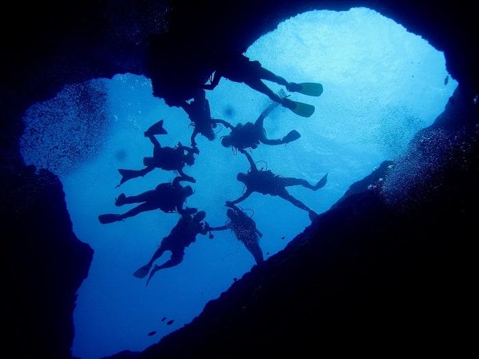 Scafandri in interiorul unei gauri albastre, la intrarea unei pesteri subterane