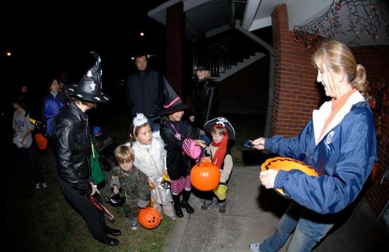 Copii si adulți mergând din ușă în ușă de Halloween